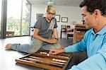 Père et fils à jouer au backgammon, à l'intérieur