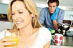 Portrait de jeune souriant verre tenue femme de jus d'orange, l'homme fatigué en arrière-plan