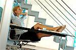 Jeune femme d'affaires reposant sur la chaise de bureau