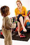 Jeune femme assise sur un canapé et en regardant son fils debout avec des jouets