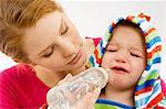 Gros plan d'une jeune femme se nourrir d'une bouteille de bébé à son fils qui pleure