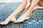 Femme frottant ses jambes au bord de la piscine