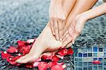 Femme masser ses jambes au bord de la piscine