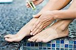 Femme en appliquant de l'huile sur ses jambes au bord de la piscine