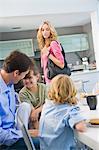 Woman standing beside her family having breakfast