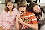 Junge chocolate Cookies mit zwei Mädchen neben ihm Essen