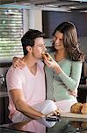 Woman feeding breakfast to a man
