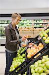 Femme acheter des pommes dans un supermarché