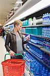 Frau Wasserflasche in einem Geschäft kaufen