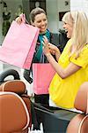 Zwei Frauen, die Spaß in der Nähe ein Auto nach dem Einkaufen
