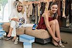 Deux femmes essayer des sandales dans une boutique