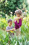 Cute little boy standing with little girl in a garden