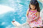 Mädchen sitzen am Rand vom Schwimmbad Blick auf Spielzeug Boot im Wasser
