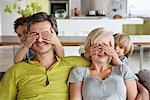 Children covering parents eyes
