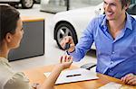Young woman handing car key to a man