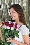 Glückliche junge Frau betrachten bunter Rosenstrauss