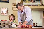 Süße kleine Junge und sein Vater kneten Teig in Küche