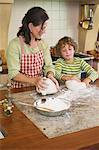 Grand-mère et petit garçon, pétrir la pâte à la cuisine