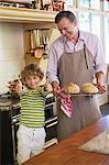 Kleiner Junge showing Thumbs up Sign mit Vater hält gebackenes Brot