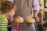 Süße kleine Junge riechen gebackenes Brot in der Hand des Vaters