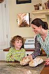 Süße kleine Junge und Mutter Brotbacken in Küche