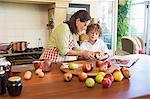 Grand-mère et petit garçon peler les fruits à la maison