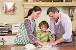Netter kleiner Junge und seine Eltern kneten Teig in Küche