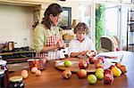 Grand-mère et petit garçon peler une pomme à la maison