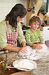 Großmutter und der kleine Junge kneten Teig in Küche