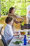 Frères et soeurs souriants organisant des aliments à table à manger avec père en arrière-plan
