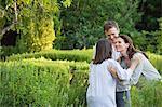 Mature Couple umarmt ihre Mutter in einem Garten