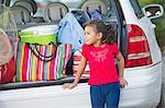 Adorable petite fille debout près de la voiture