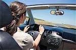 Young woman driving a convertible car