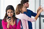 Porträt von Studenten mit einem Mobiltelefon während Freunde suchen nach Test Ergebnisse in Schwarzes Brett