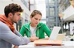 University students using laptop in lobby