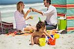 Griller le couple avec boisson tandis que leur fille jouant sur la plage