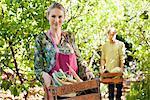 Femme souriante tenant un cageot de radis