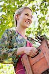 Femme souriante tenant un cageot de légumes
