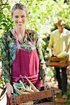 Femme souriante tenant une caisse de radis