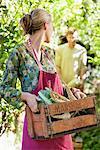 Jeune femme tenant une caisse de radis