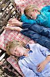 Tired little siblings sleeping in hammock