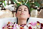 Belle jeune femme détente dans la baignoire avec pétales