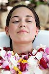 Belle jeune femme se détendre dans la baignoire avec pétales