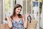 Woman holding shopping bag and smiling, Paris, Ile-de-France, France