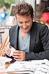 Man reading a magazine in a restaurant, Paris, Ile-de-France, France