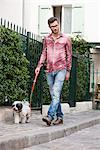 Man holding a dog on leash walking on a sidewalk, Paris, Ile-de-France, France