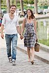 Couple walking near a canal and smiling, Paris, Ile-de-France, France