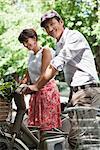 Couple riding bicycles and smiling, Paris, Ile-de-France, France