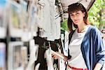 Woman holding a book at a book stall, Paris, Ile-de-France, France