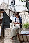Woman reading a book at a book stall, Notre Dame de Paris, Paris, Ile-de-France, France